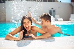 La jeune adolescente criarde à la piscine a ennuyé avec l'éclaboussement de piscine Éclaboussant l'eau et jouant des jeux à la pi Image stock