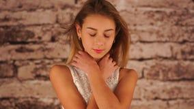 La jeune adolescente dans la robe blanche reste près du mur, s'étreignant, dansant, regardant l'appareil-photo et le sourire clips vidéos