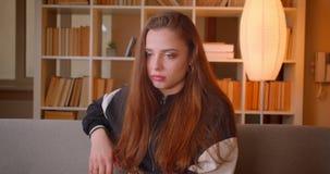 La jeune adolescente en verres 3d observe le thriller à la TV étant attentive et concentrée sur le fond d'étagères à banque de vidéos