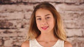 La jeune adolescente reste près du mur, regardant l'appareil-photo et le sourire Le vent souffle et son cheveu banque de vidéos