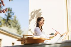 La jeune artiste de sourire de femme de brune peint un tableau sur la rue, pr?s d'un bel arbre de magnolia photos libres de droits