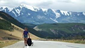 La jeune auto-stoppeuse de touristes de femme tire un sac à dos lourd sur une route de montagne Il y a des montagnes de neige dan clips vidéos