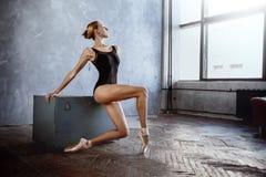 La jeune ballerine dans un costume de danse noir pose dans un studio de grenier image stock