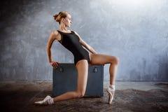 La jeune ballerine dans un costume de danse noir pose dans un studio de grenier image libre de droits