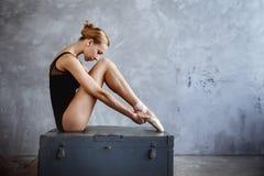La jeune ballerine dans un costume de danse noir pose dans un studio de grenier images stock