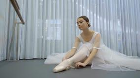 La jeune ballerine lie ses orteils de point se reposant sur le plancher dans le studio lumineux banque de vidéos