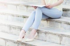 La jeune belle étudiante lit sur des escaliers image libre de droits