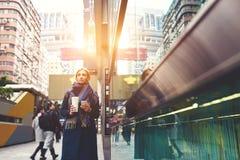 La jeune belle blonde voyage par le travail utilisant le navigateur et l'Internet 4G rapide en errant fasciné par des bâtiments Photos stock