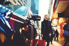 La jeune belle blonde voyage par les amis de attente de travail se tenant dehors près de l'automobile de location Photo libre de droits