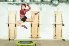 La jeune belle et attirante fille sautent sur le trempoline, foyer sélectif avec la tache floue de mouvement photographie stock