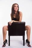 La jeune belle femme aux pieds nus renversante écarte les jambes le cuir noir Photographie stock libre de droits