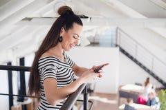 La jeune belle femme avec les cheveux bruns se tient à l'intérieur et tient un smartphone Une femelle avec du charme de brune dan Images libres de droits