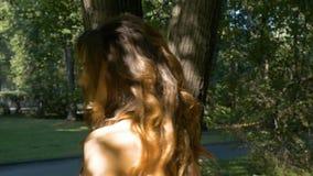 La jeune belle femme avec les cheveux rouges marche en parc banque de vidéos