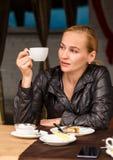 La jeune belle femme avec une tasse de café dans un café extérieur, fille prennent le déjeuner sur la terrasse images stock