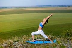 La jeune belle femme blonde faisant le yoga s'exerce sur une roche Photo libre de droits