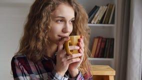 La jeune belle femme boit du café banque de vidéos