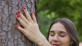 La jeune belle femme caresse l'arbre, l'amour de la nature, la paix se sentante et l'unité banque de vidéos