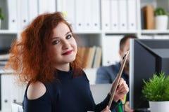 La jeune belle femme d'une chevelure rouge s'asseyent à la table dans le bureau dans le coffret de son patron Photos libres de droits