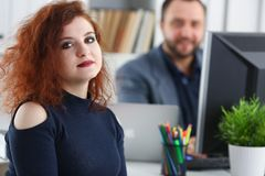 La jeune belle femme d'une chevelure rouge s'asseyent à la table dans le bureau dans le coffret de son patron Photo libre de droits