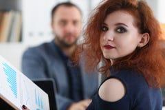 La jeune belle femme d'une chevelure rouge s'asseyent à la table dans le bureau dans le coffret de son patron Image stock