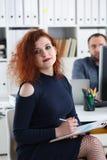 La jeune belle femme d'une chevelure rouge s'asseyent à la table dans le bureau dans le coffret de son stylo de prise de patron d Photo stock