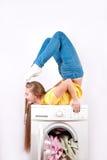 La jeune belle femme dans des blues-jean s'assied sur une machine à laver ayant flâné comme un gymnaste d'isolement contre un bla Images libres de droits