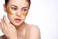 La jeune belle femme dans des corrections d'or pour des yeux sur le blanc a isolé le fond, soins de la peau de visage image stock