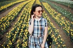La jeune belle femme dans des lunettes de soleil avec les tulipes jaunes fleurit dans le jardin Photographie stock libre de droits