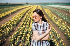 La jeune belle femme dans des lunettes de soleil avec les tulipes jaunes fleurit dans le jardin Photos stock