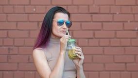 La jeune belle femme dans des lunettes de soleil boit le cocktail de limonade d'un pot en verre avec une paille sur le fond banque de vidéos