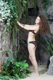 La jeune belle femme dans le bikini se tient près à de grandes roches images stock