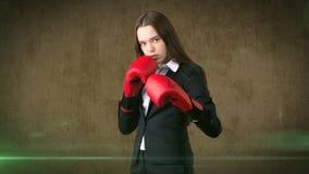 La jeune belle femme dans le costume noir et la chemise blanche se tenant dans le combat posent avec les gants de boxe rouges Con photographie stock