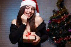 La jeune belle femme dans la robe de soirée et la Santa couvrent tenir un g Images libres de droits