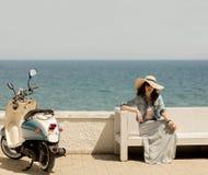 La jeune belle femme dans une longue jupe s'assied sur un banc sur le bord de mer photo libre de droits