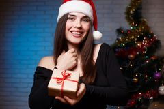 La jeune belle femme de sourire dans la robe de soirée et la Santa couvrent l'esprit Image stock