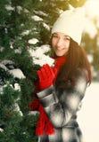 La jeune belle femme derrière la neige a couvert le pin photographie stock libre de droits