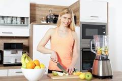 La jeune belle femme fait un smoothy avec un mélangeur Image stock
