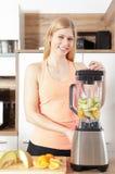 La jeune belle femme fait un smoothy avec un mélangeur Photo libre de droits