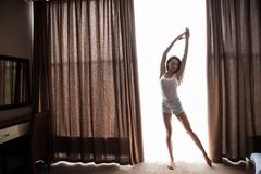 La jeune belle femme heureuse baîlle et soulève ses mains, se tenant à côté du lit dans sa chambre à coucher à la maison Images libres de droits