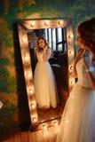 La jeune belle femme lisse près du miroir avec des lampes photo stock