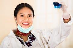 La jeune belle femme s'est habillée dans les médecins enduisent et collier rouge, masque facial abaissé au menton, supportant le  Photo stock