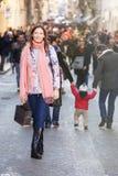 La jeune belle femme se tient dans une foule des citoyens Image libre de droits