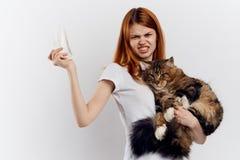 La jeune belle femme sur un fond clair tient un chat, les émotions, une allergie aux animaux familiers Photos stock