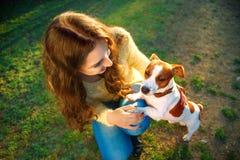 La jeune belle femme tient une remise la patte du ` s de chien sur un fond de parc de ressort photo stock