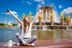 La jeune belle femme a un repos se reposant près de la fontaine Images libres de droits