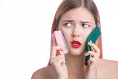 La jeune belle fille avec l'expression drôle emploie des éponges pour le nettoyage facial profond, enlevant composent images stock