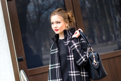 La jeune belle fille avec le sac à la mode se tient sur le s Images stock