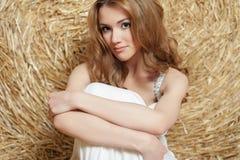 La jeune belle fille avec les cheveux rouges dans une robe blanche s'assied près d'une meule de foin Été dans le village photos stock