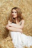 La jeune belle fille avec les cheveux rouges dans une robe blanche s'assied près d'une meule de foin Été dans le village Images libres de droits