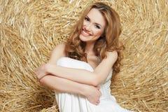 La jeune belle fille avec les cheveux rouges dans une robe blanche s'assied près d'une meule de foin Été dans le village Photographie stock libre de droits